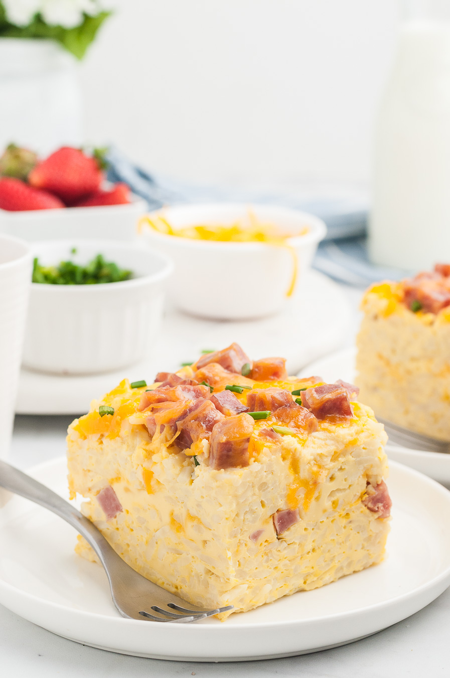 breakfast casserole serving on a plate alongside a fork. Strawberries, sliced green onions and cheddar cheese in individual bowls in the background.