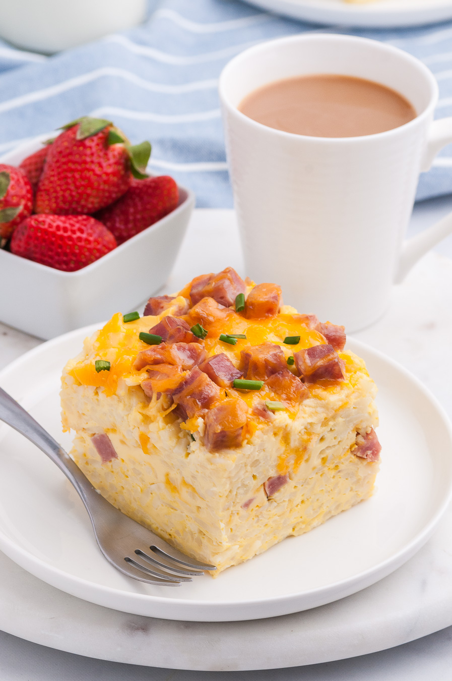 brunch casserole with ham and cheddar cheese made in the slow cooker. Serving placed on a plate and served next to coffee mug and fresh strawberries.