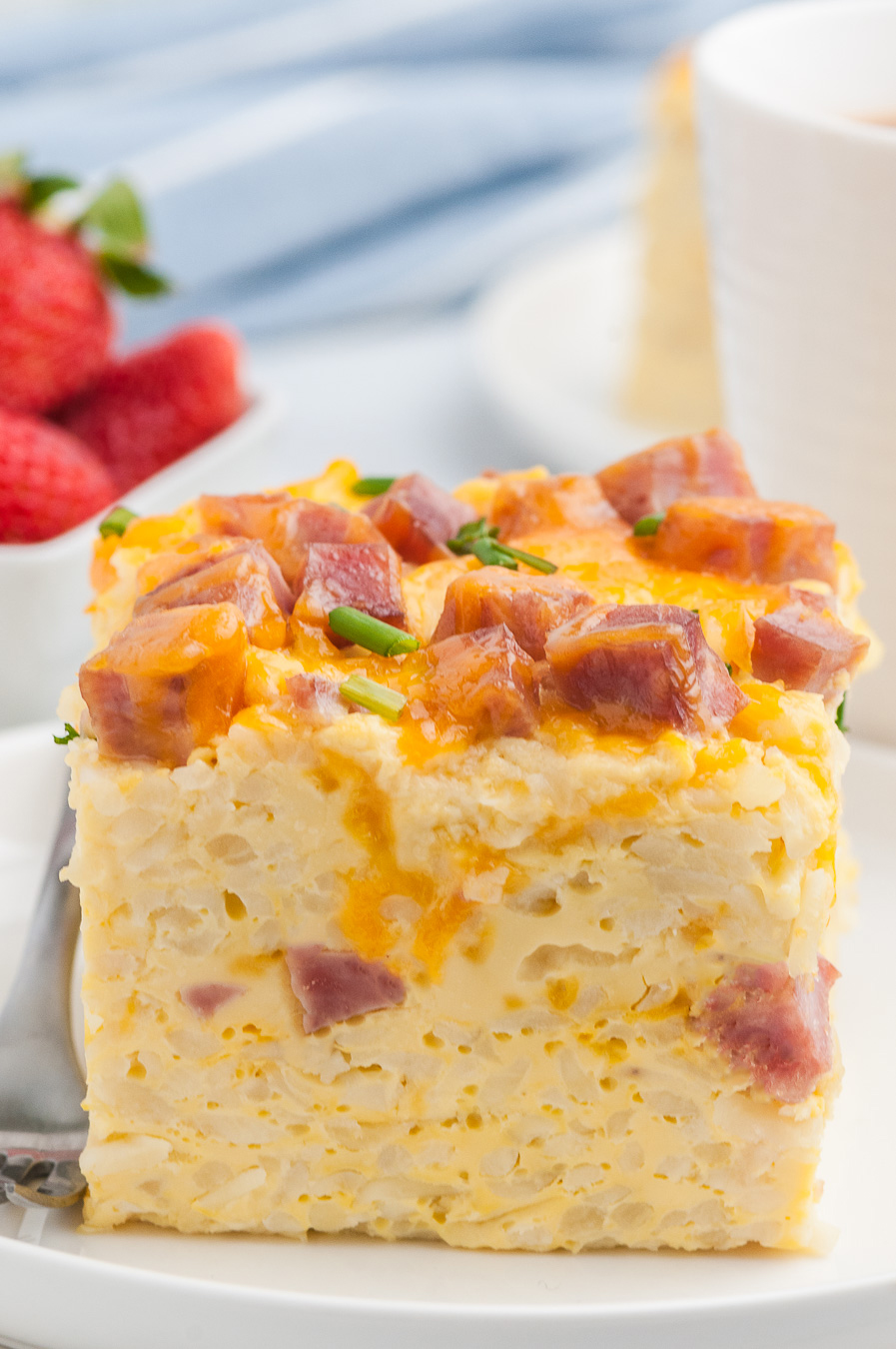 hearty slice of breakfast casserole sliced into a square portion. Strawberries and coffee mug in background.