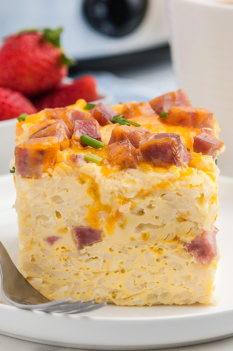 individual slice of ham and cheddar casserole served on a white plate with a lip.