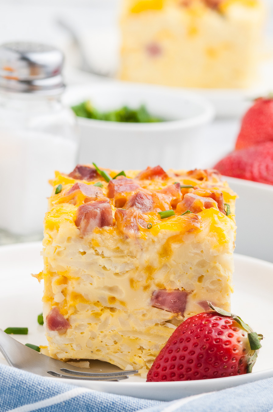 tall breakfast casserole on a dish with chunks of ham showing through. Paired with a fresh strawberry garnish. Hint of blue napkin near plate.