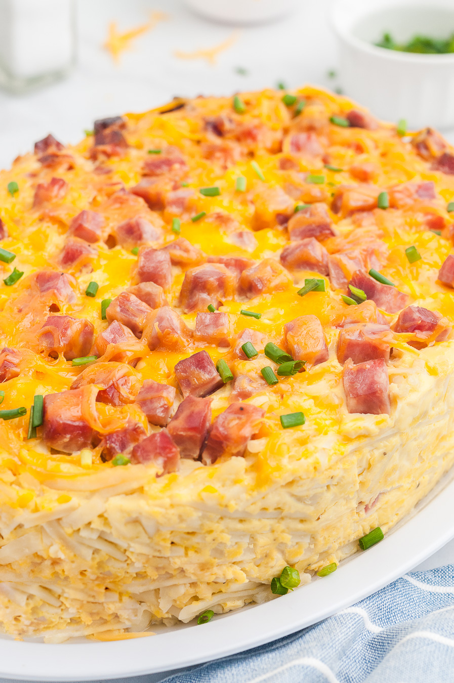 Ham and cheddar breakfast casserole prepared in an oval slow cooker, placed onto a plate for serving.