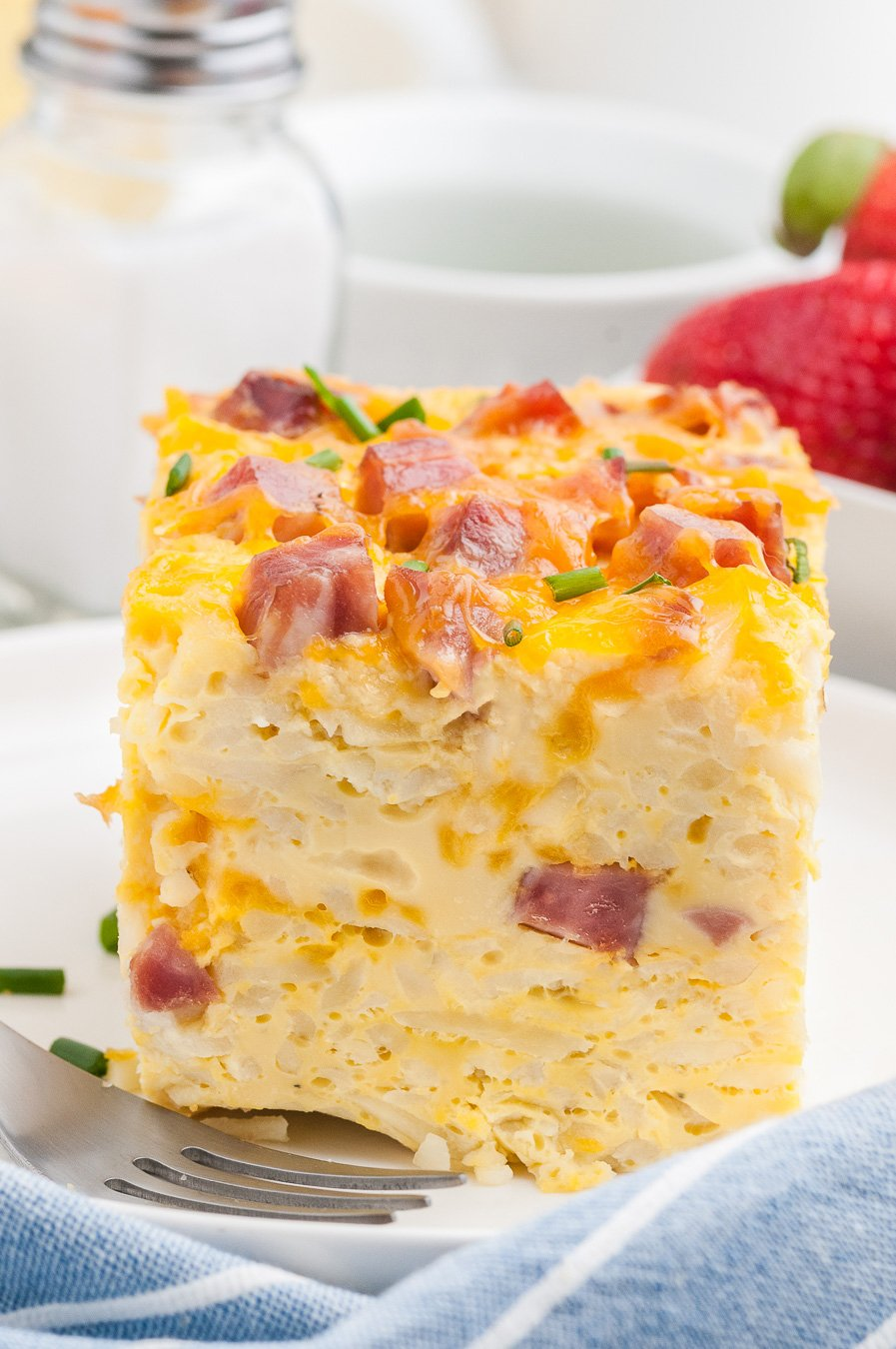 huge slice of breakfast casserole. Tall slice of egg casserole with ham and cheddar.