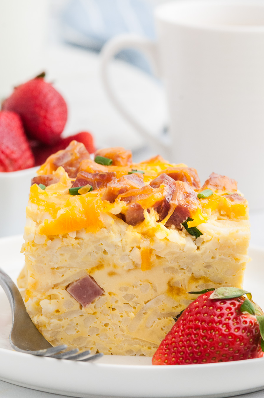 up close view of tall egg breakfast casserole. Fresh strawberry garnish.