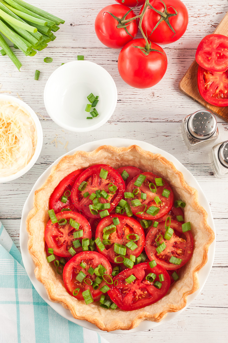 green onions being added to a tomato pie