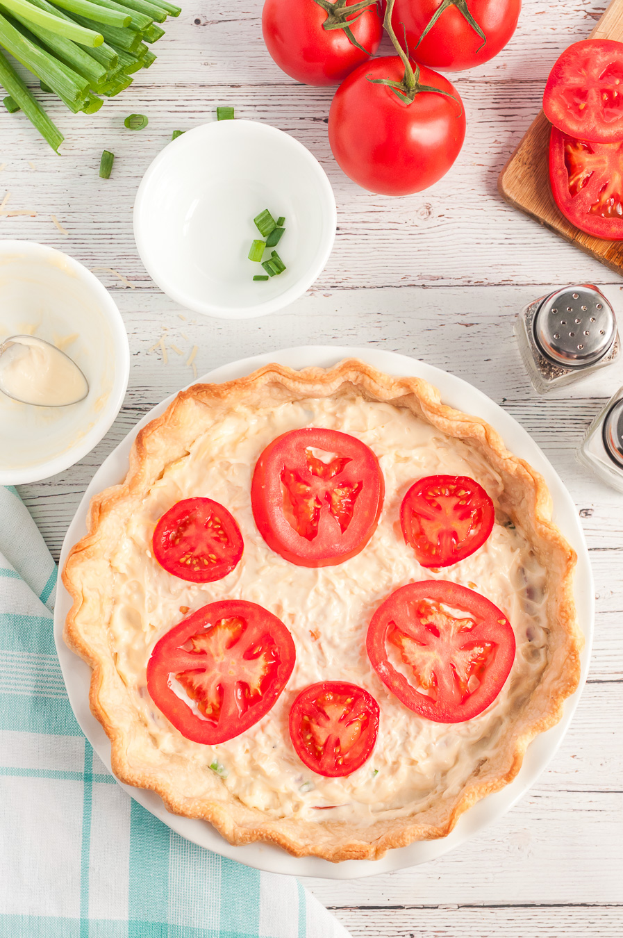 Adding a layer of sliced tomatoes to tomato pie