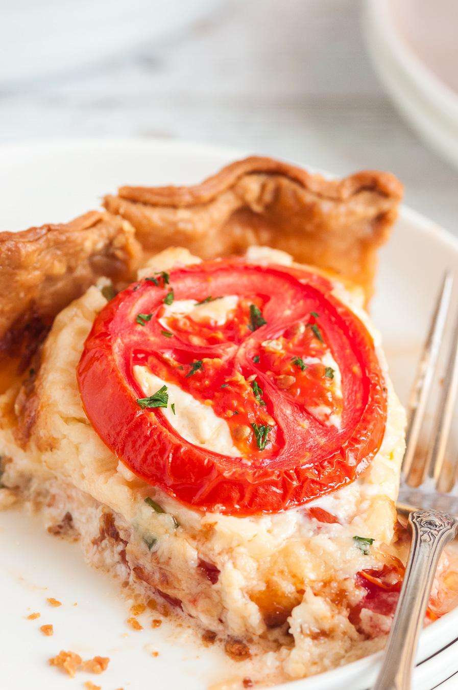 tomato pie slice up close with fresh tomato garnish