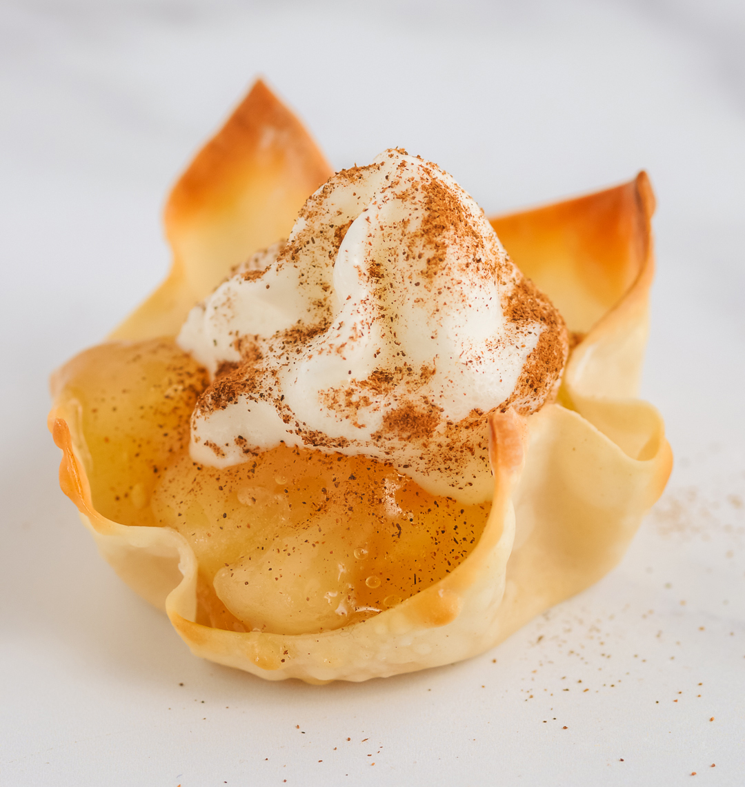 apple pie cups up close with apple pie filling, whipped cream and cinnamon