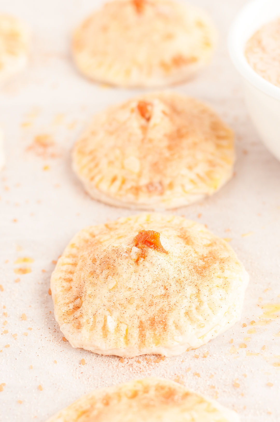 adding sugar and spice blend to mini pies