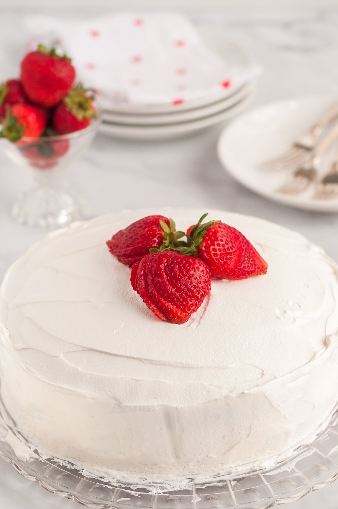 frosted cake topped with sliced strawberries
