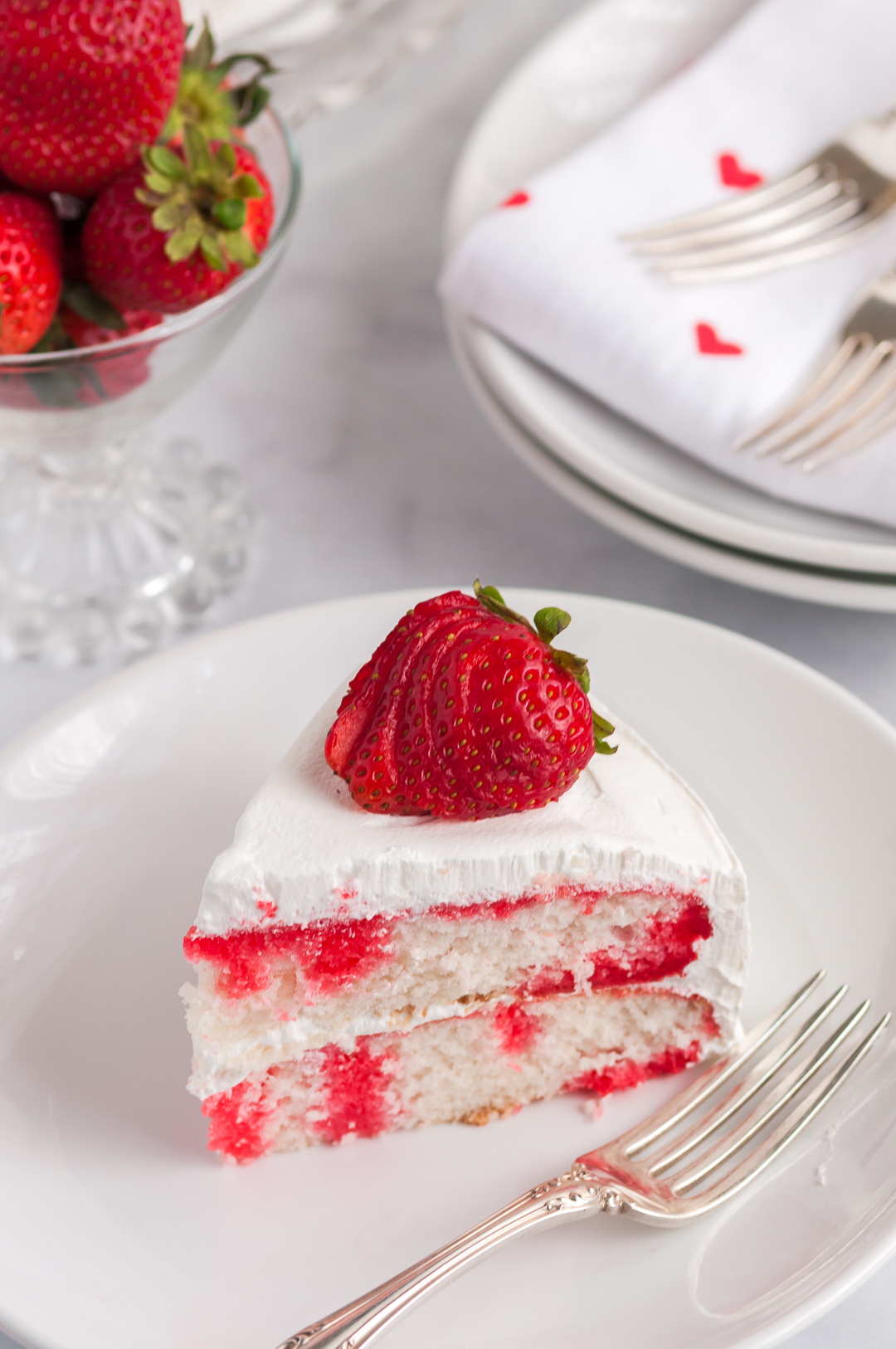 plated slice of strawberry poke cake