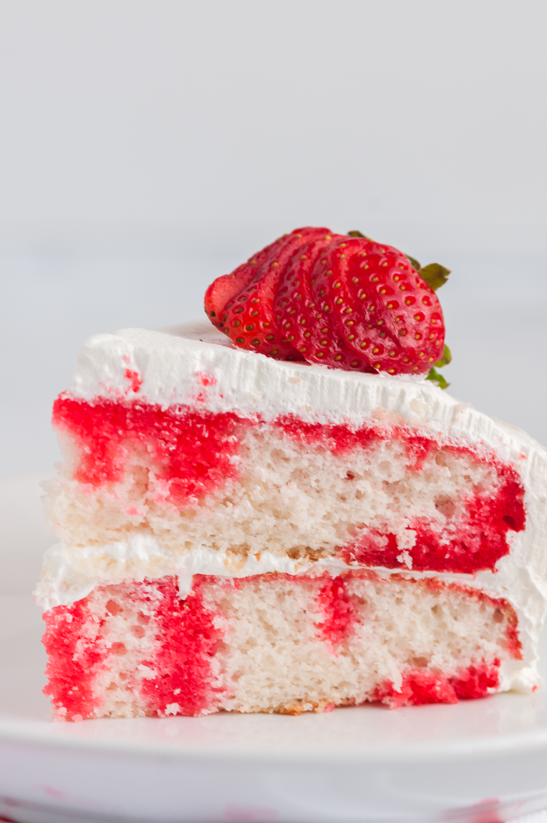 slice of strawberry poke cake on a plate