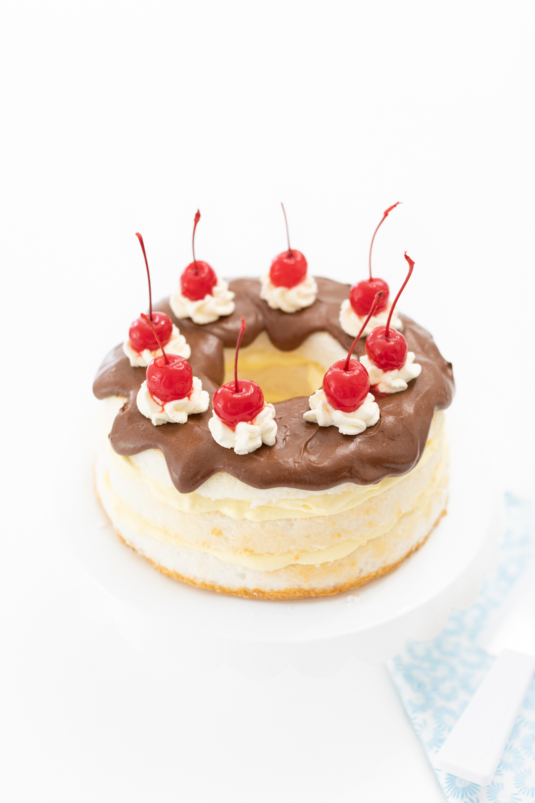 pretty chocolate covered cake with layers of pudding and topped with pretty cherries