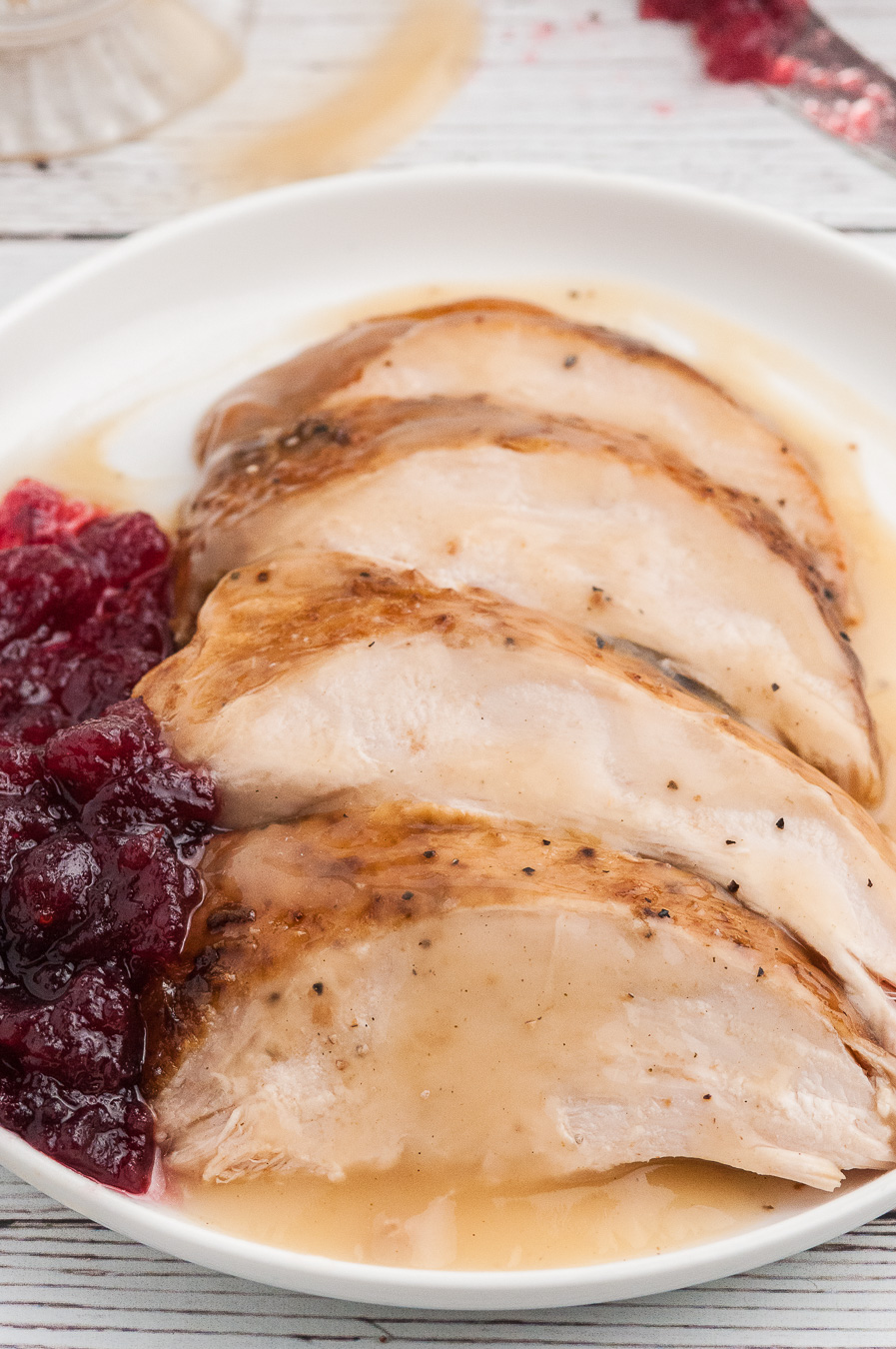 sliced turkey on a plate served with cranberry sauce