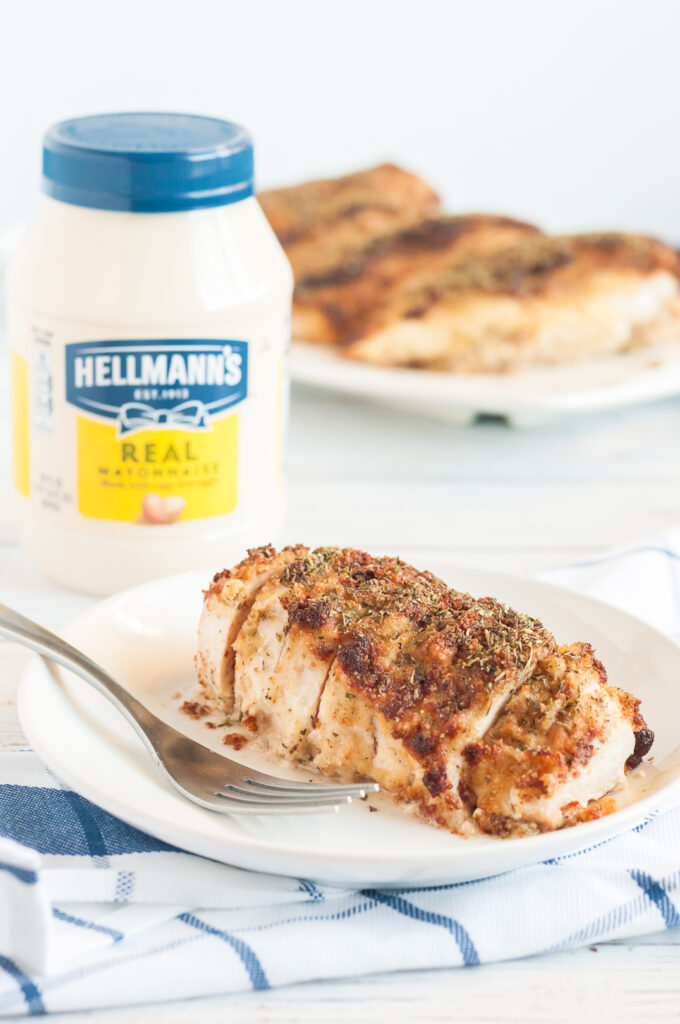 moist baked chicken with parmesan crust on top. mayo jar in the background