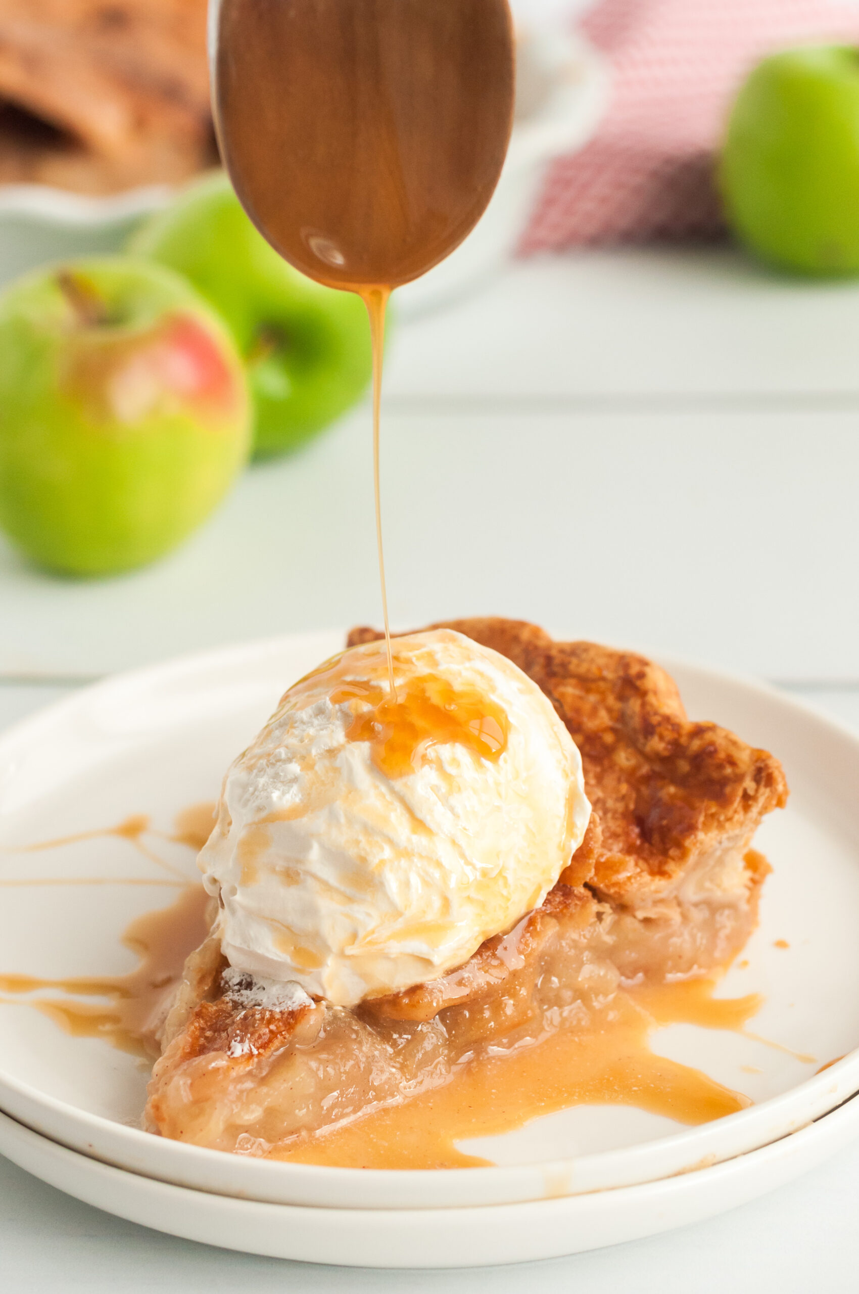 apple pie slice on a plate with caramel being drizzled on top