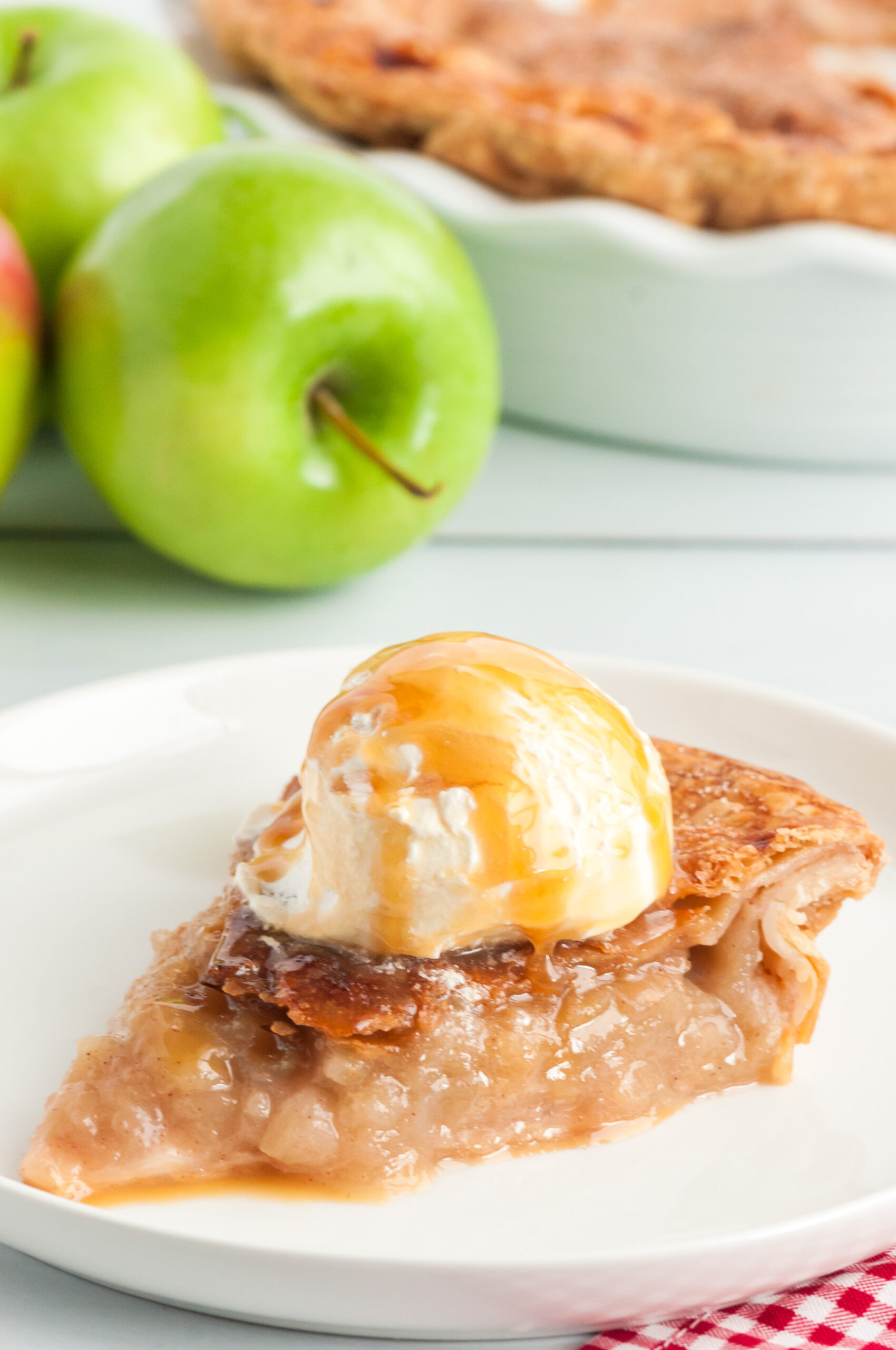 single slice of hot apple pie with ice cream and caramel drizzle on top. fresh apples in background.