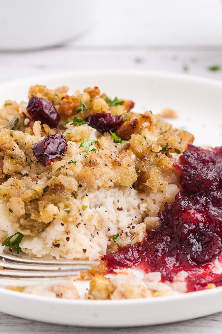 serving of stuffing casserole on a plate with cranberry sauce