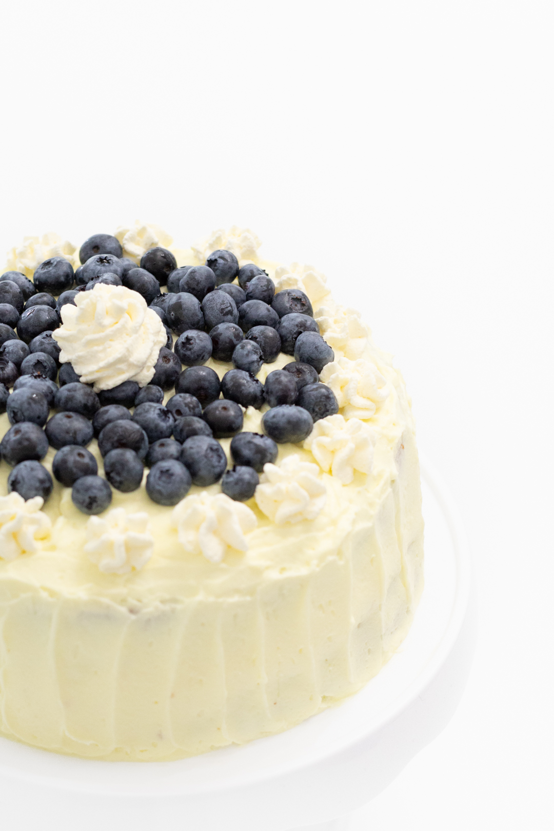 Lemon frosted cake with fresh blueberries on top.
