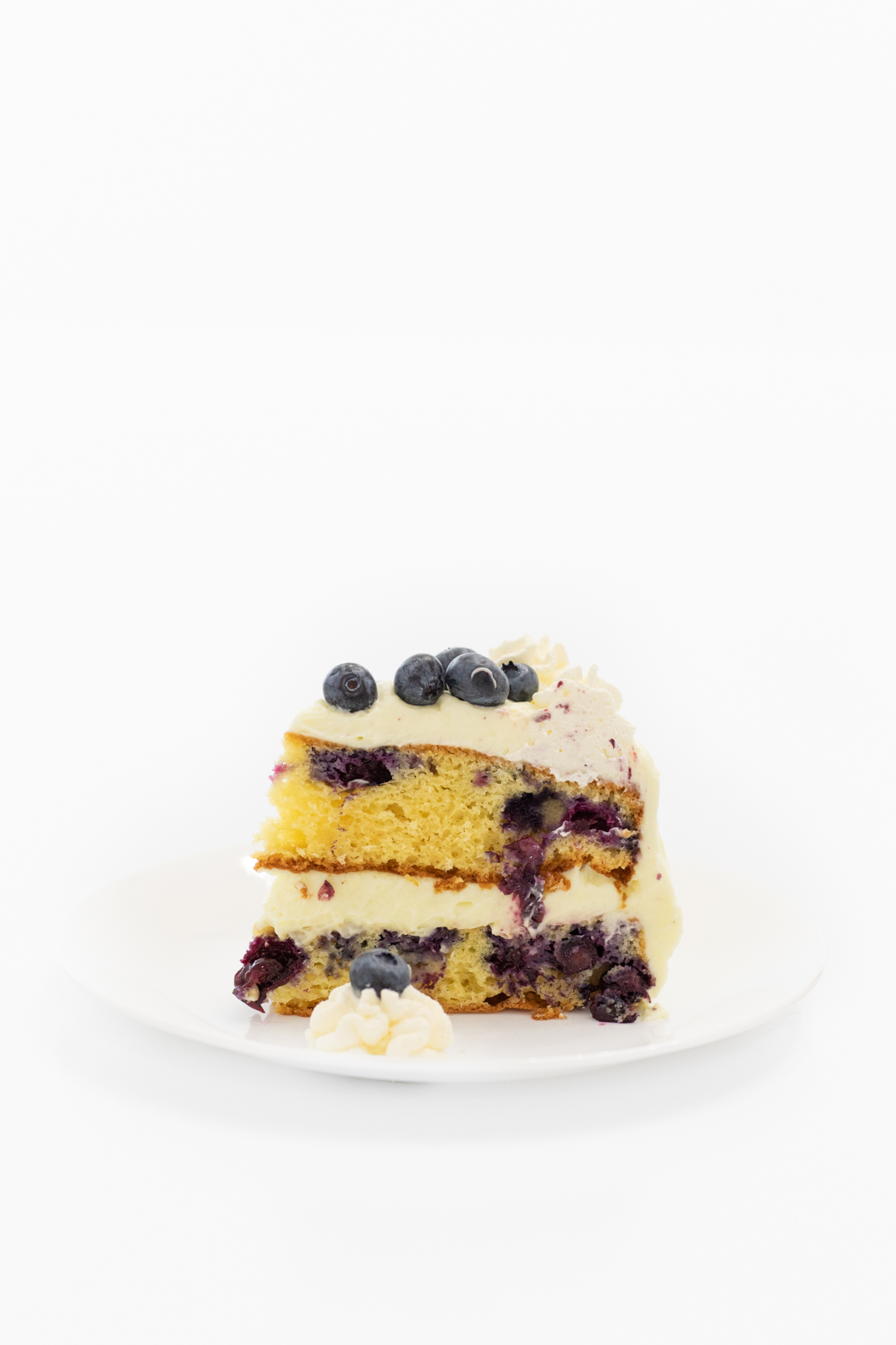 Tall slice of blueberry cake with fresh blueberries