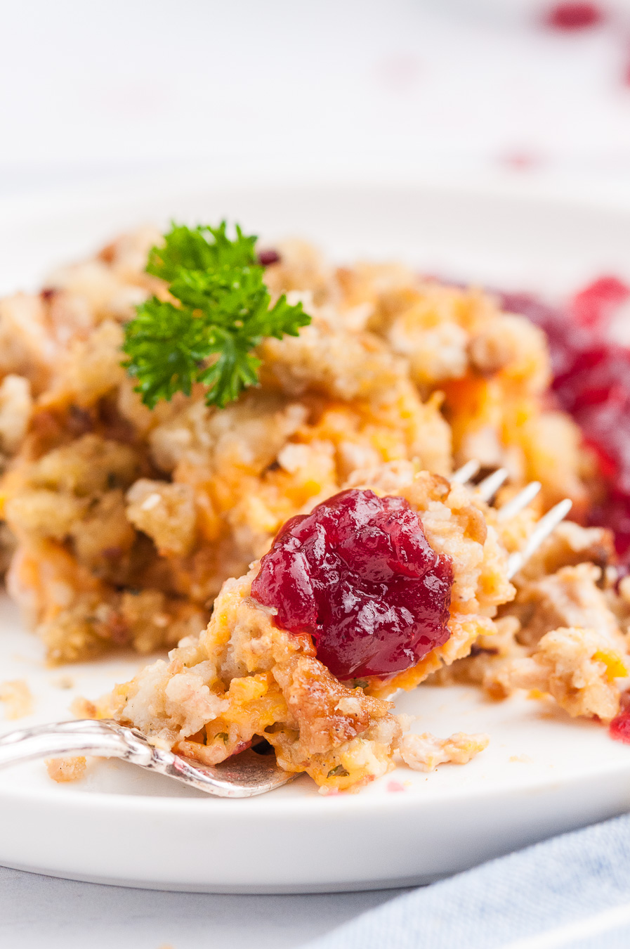 fork full of stuffing casserole with cranberry sauce