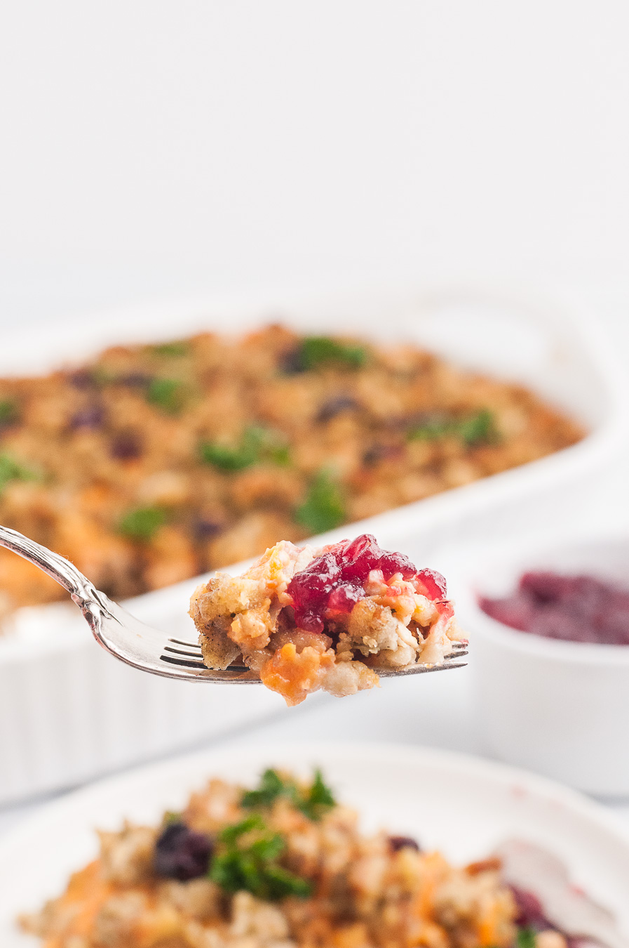 fork full of stuffing casserole with a dab of cranberry sauce
