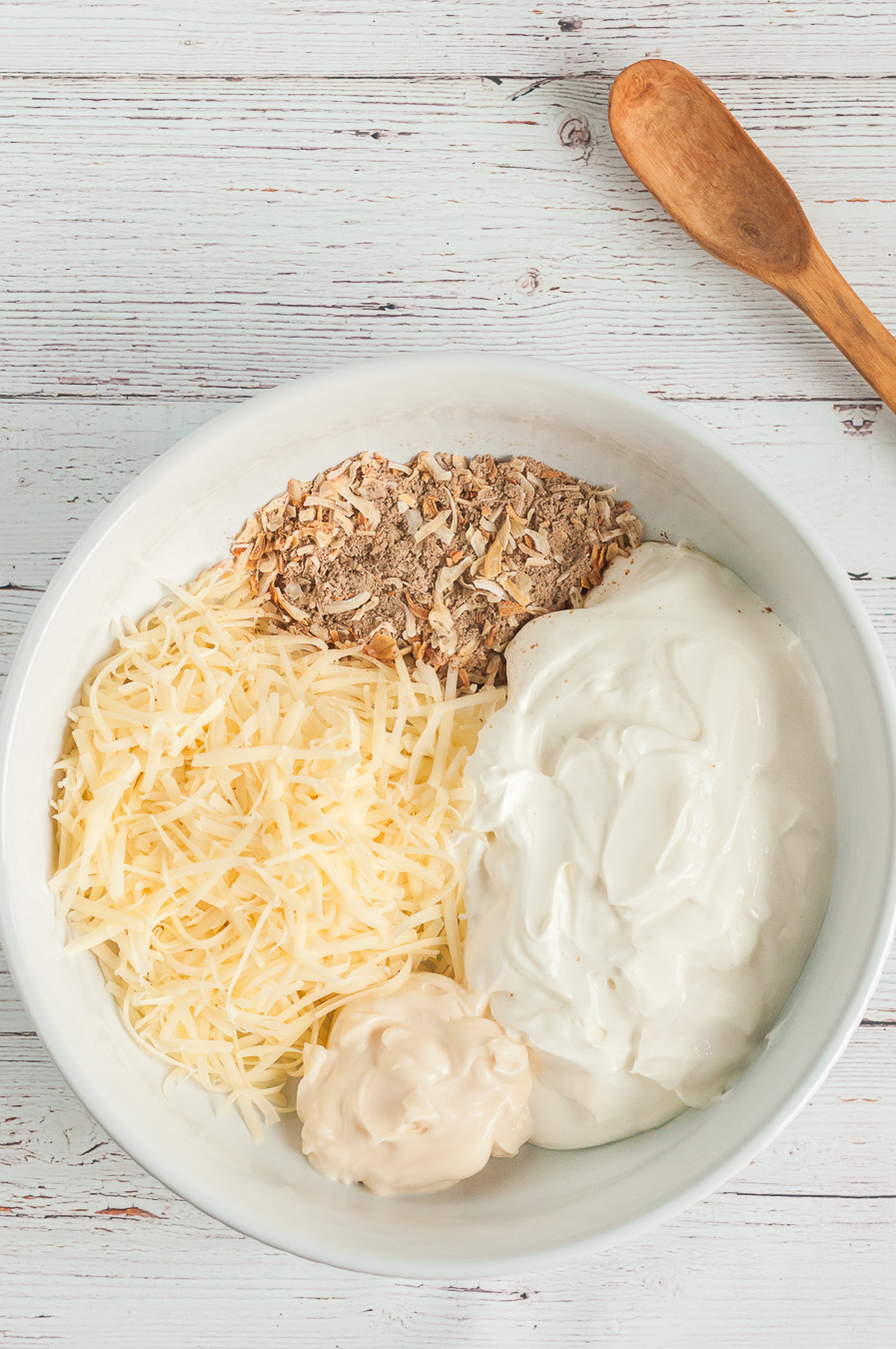 ingredients for french onion dip in a mixing bowl