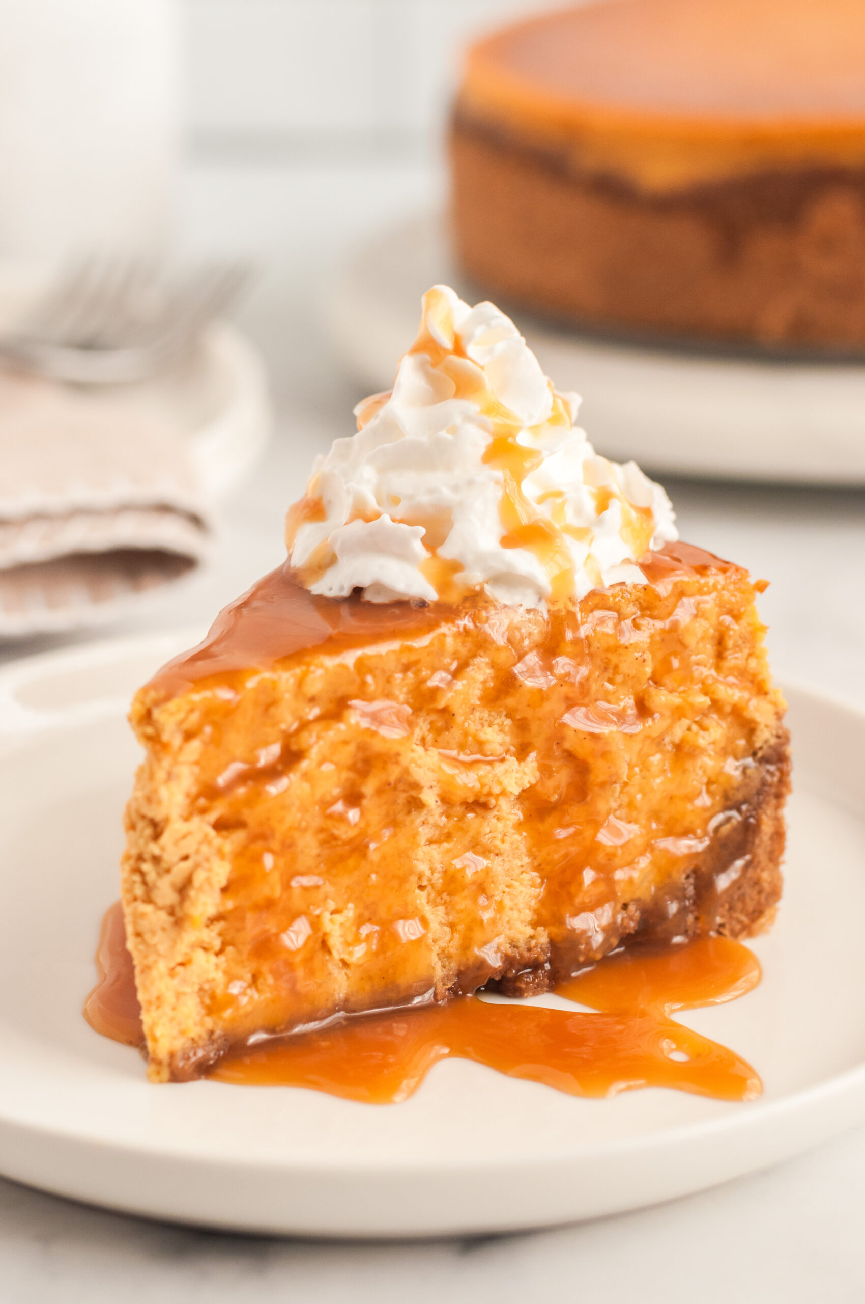 perfect slice of cheesecake on a plate topped with caramel and whipped cream