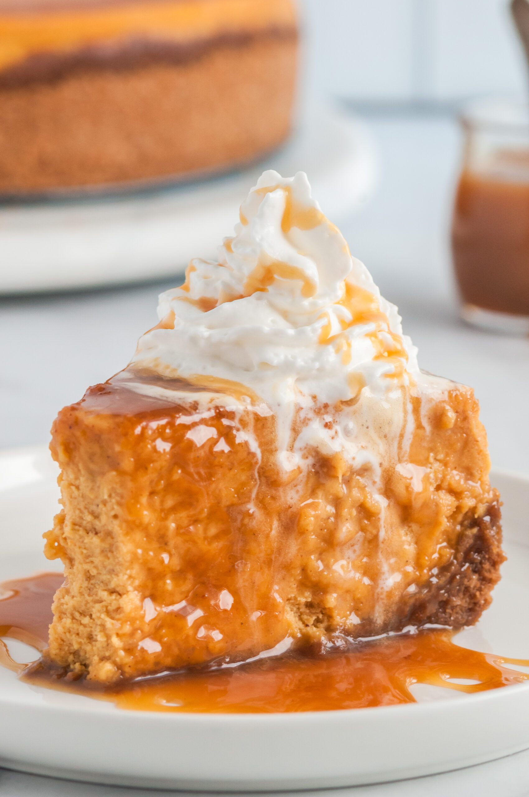plated slice of pumpkin cheesecake with caramel sauce and whipped cream on top