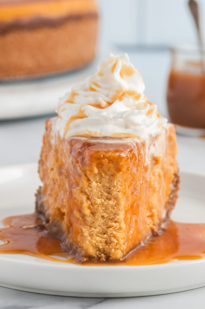 slice of pumpkin pie with fork bite taken out of it. Drizzled with caramel and whipped cream. Ginger crust.