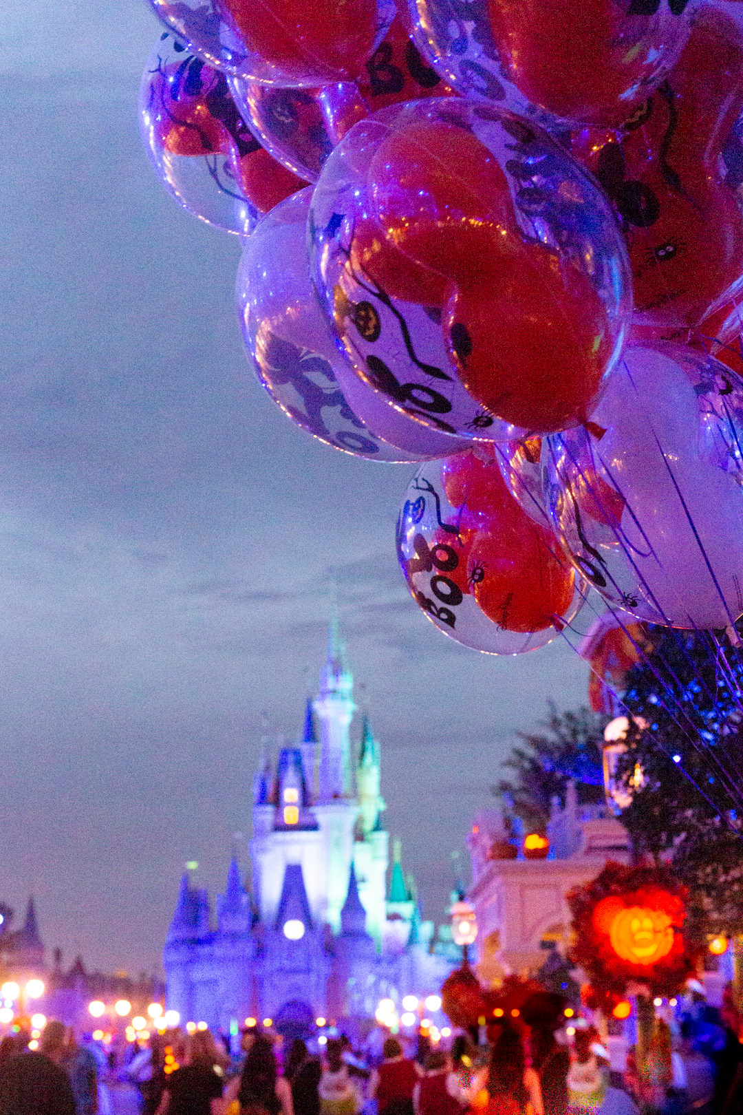 mickey's not so scary party night photo down main street with halloween balloons