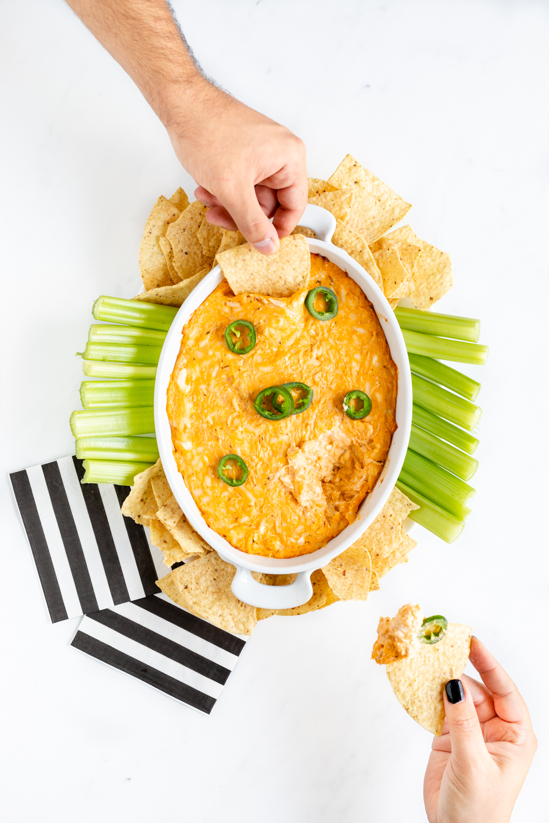 girl holding tortilla chip with dip
