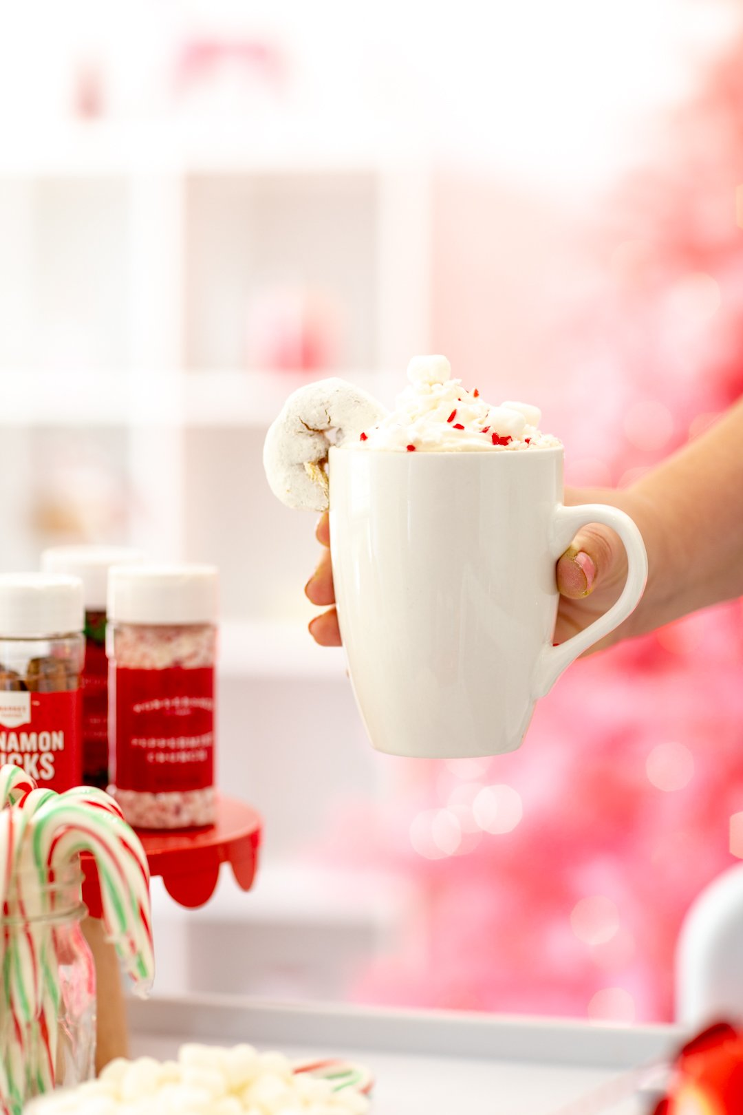 holding mug with whipped cream and candy cane