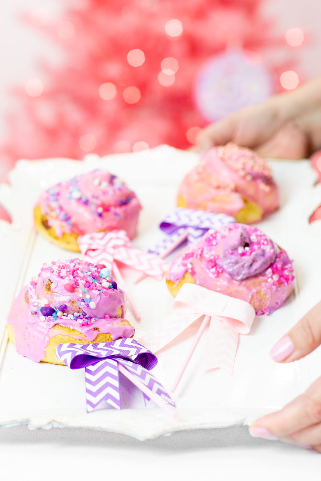 Pink and purple cinnamon roll lollipops with bows.