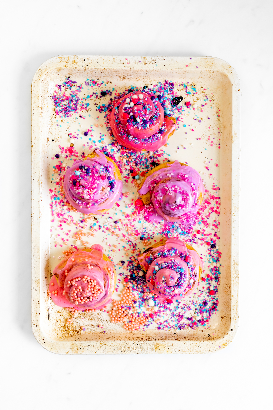 pink cinnamon rolls with colorful sprinkles