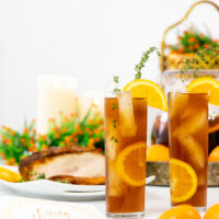 glasses filled with iced tea, orange slices and thyme