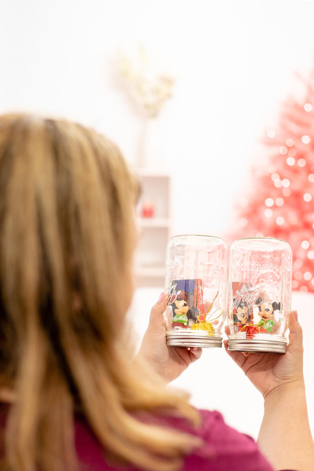disney ornaments in jars being held