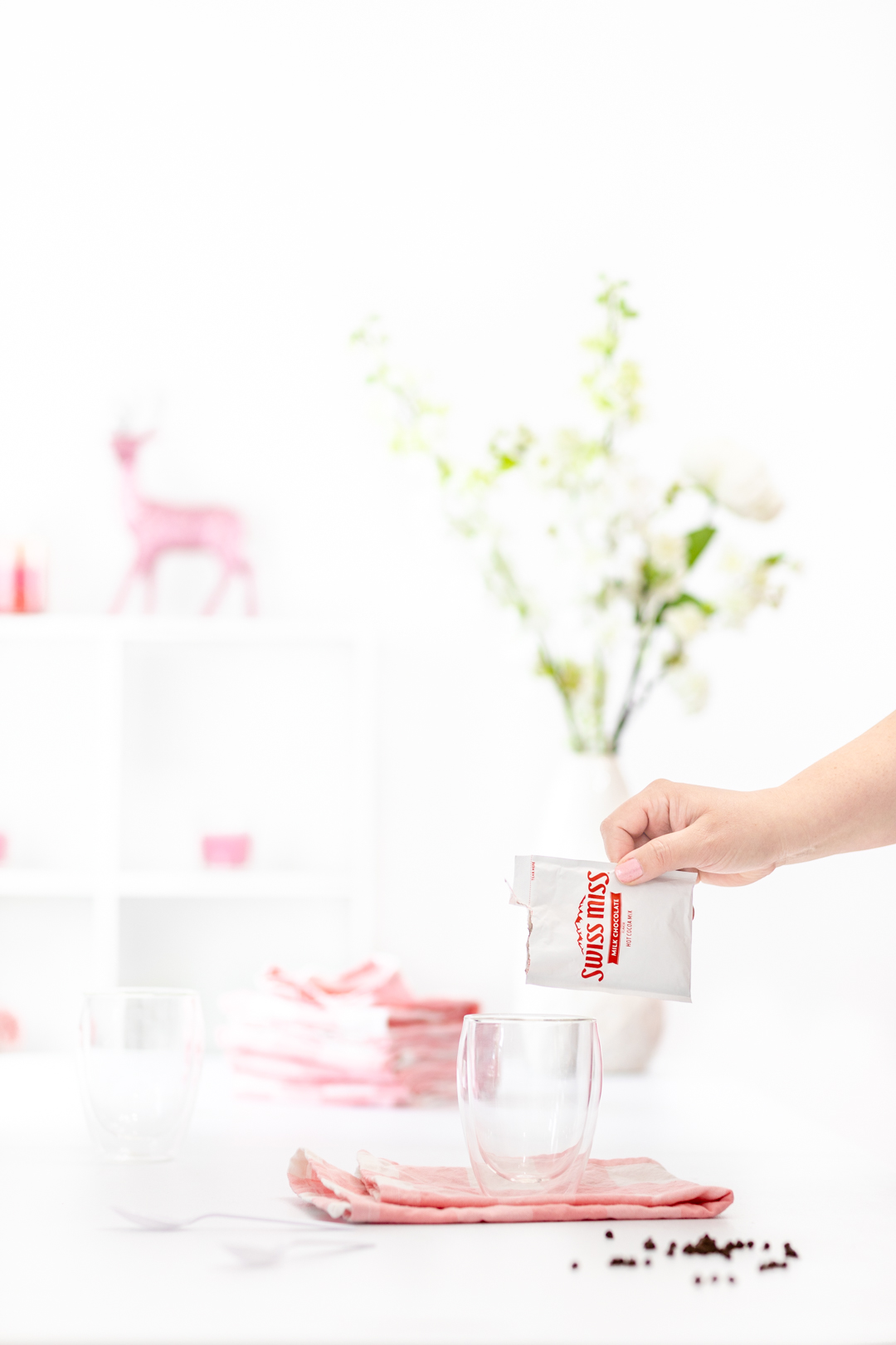 Pouring a packet of Swiss Miss into a mug.