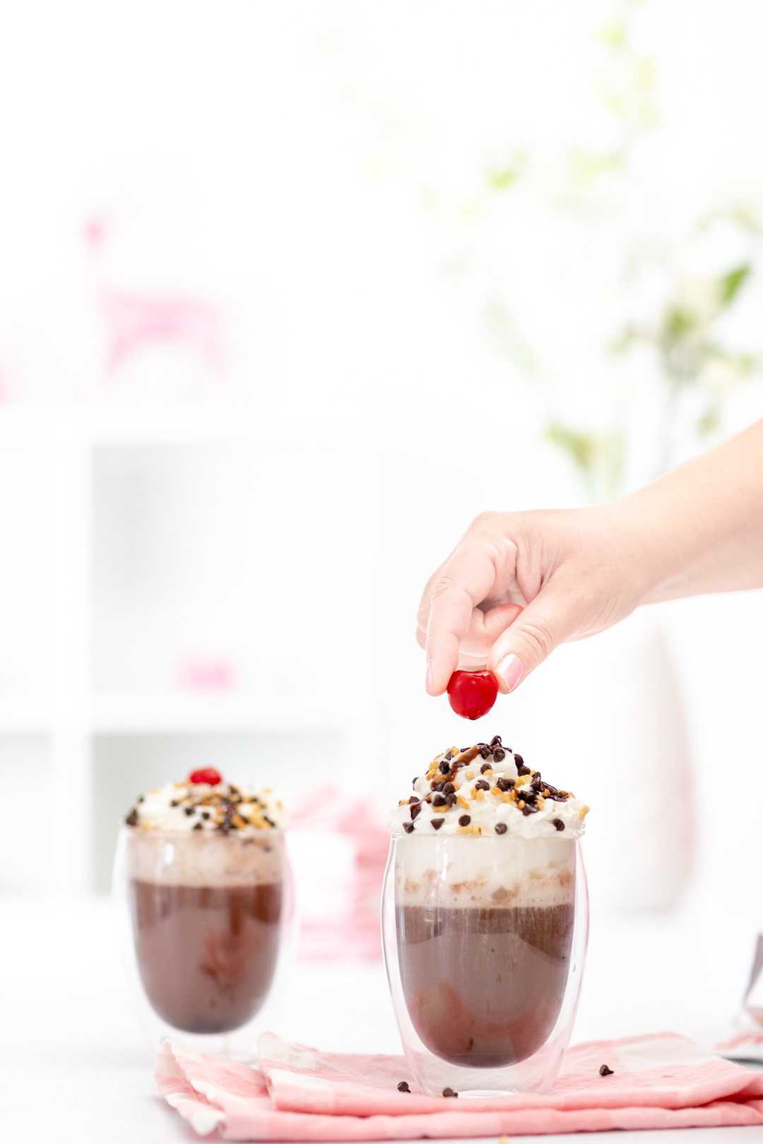 placing cherry on top of hot cocoa and whipped cream