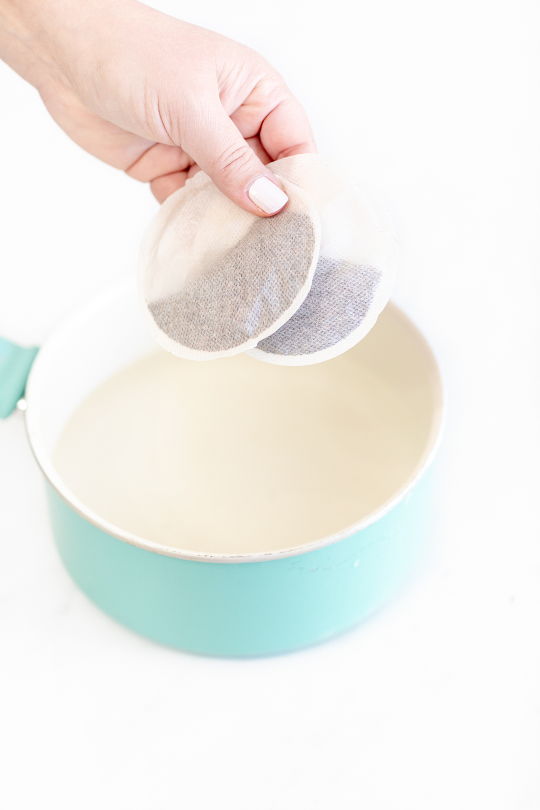 placing round iced tea bags into a potplacing round iced tea bags into a pot