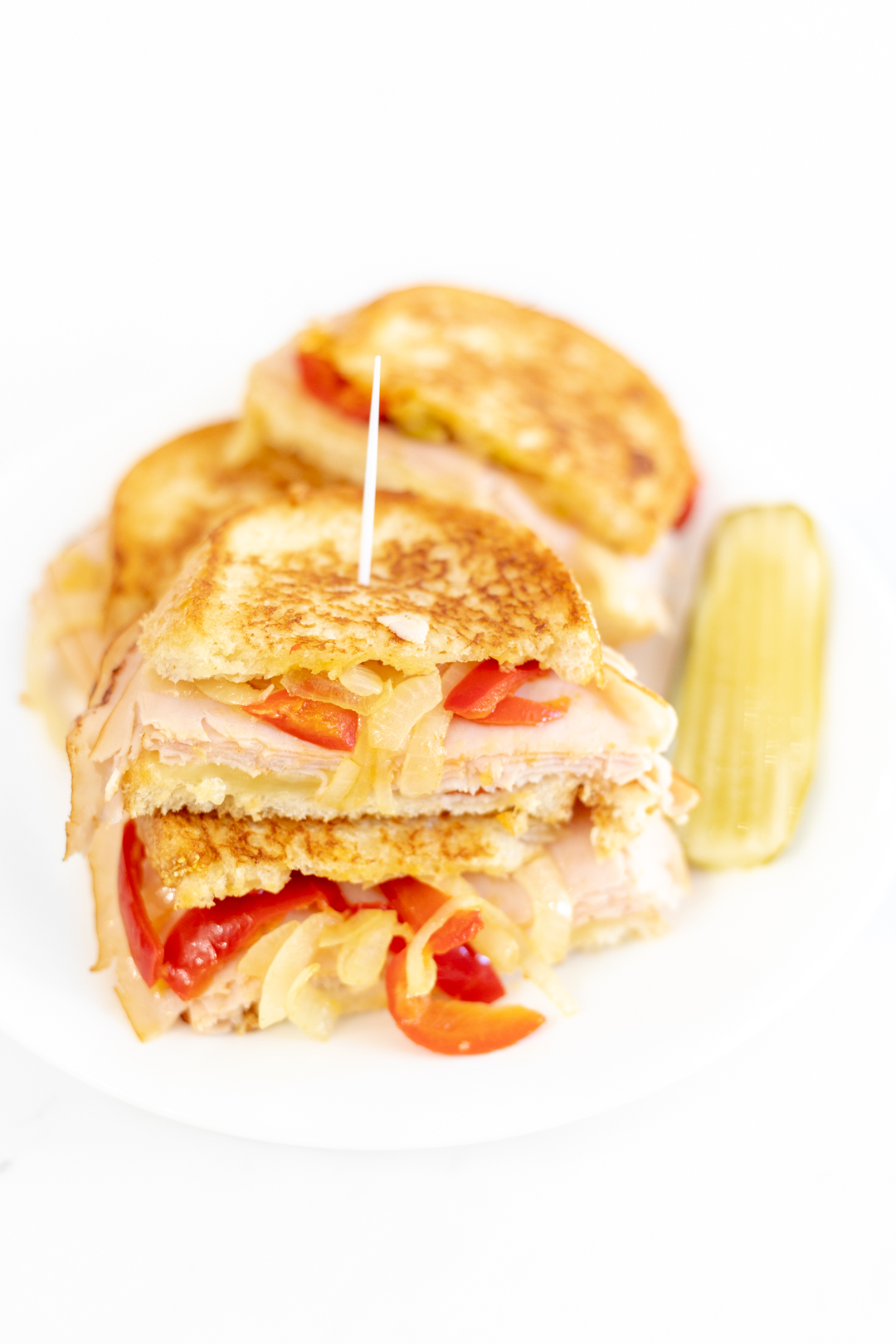 grilled sandwich with cheese, turkey, peppers and onions
