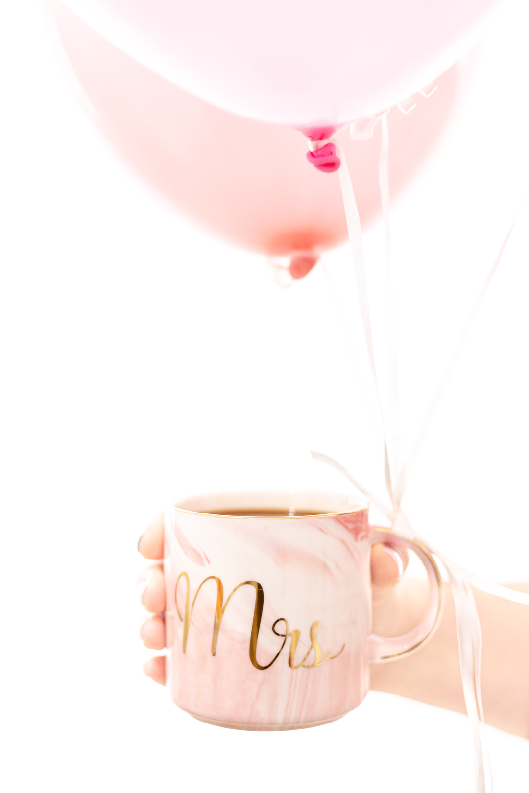 Mug of coffee with balloons tied to it for a surprise