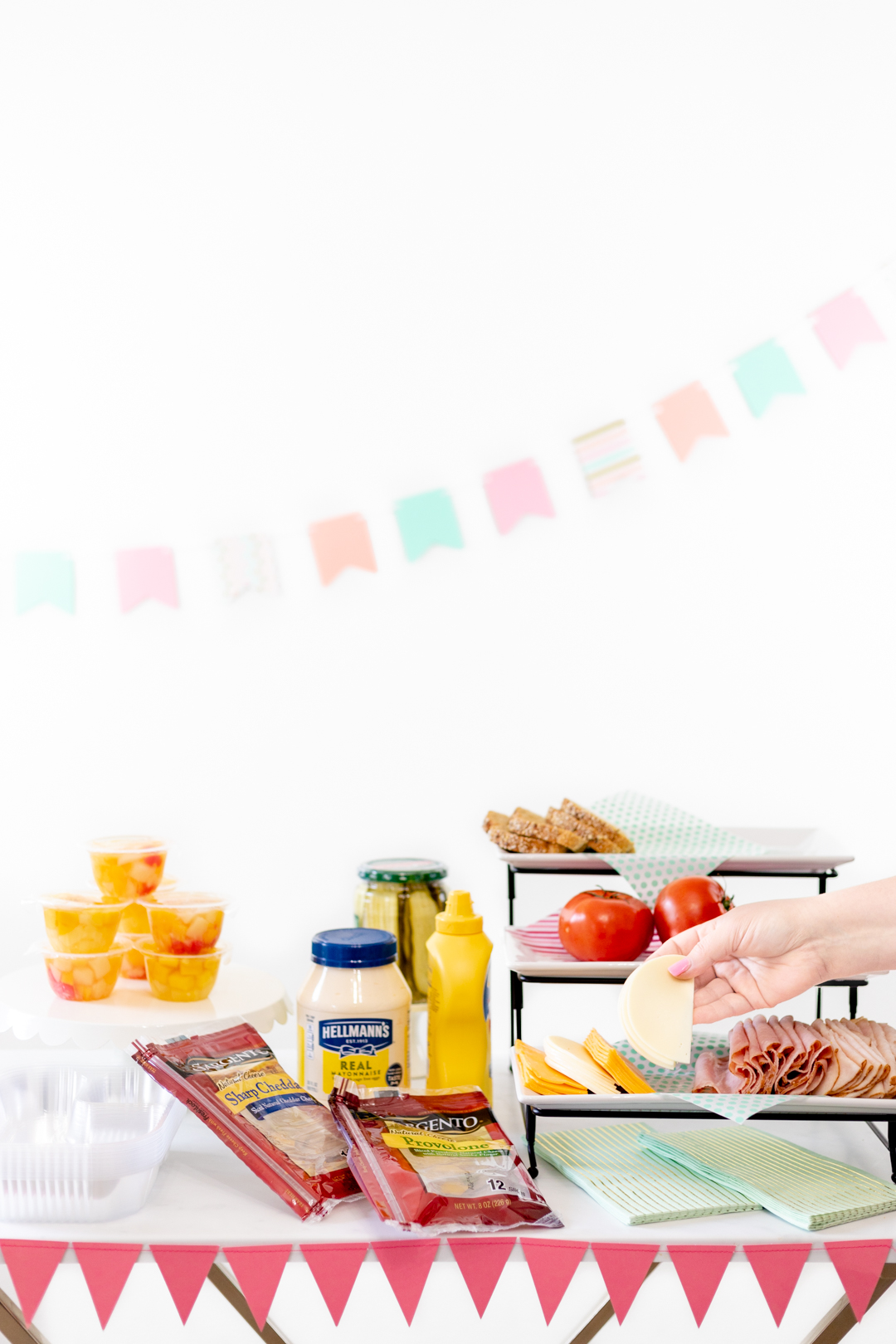 sandwich party spread with all the fixings and side options like fruit.