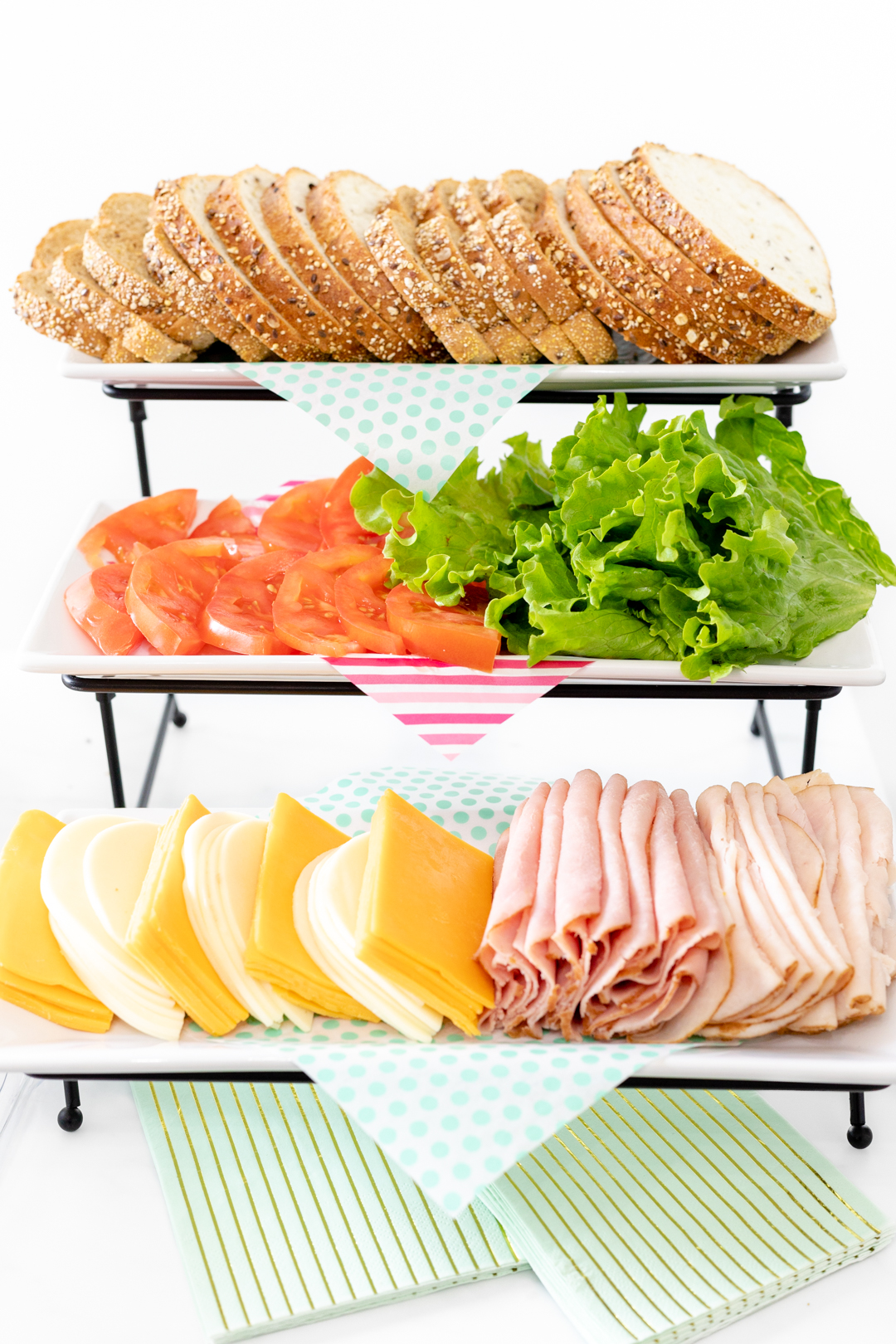sandwich buffet station with bread, vegetables, cheese and meats.
