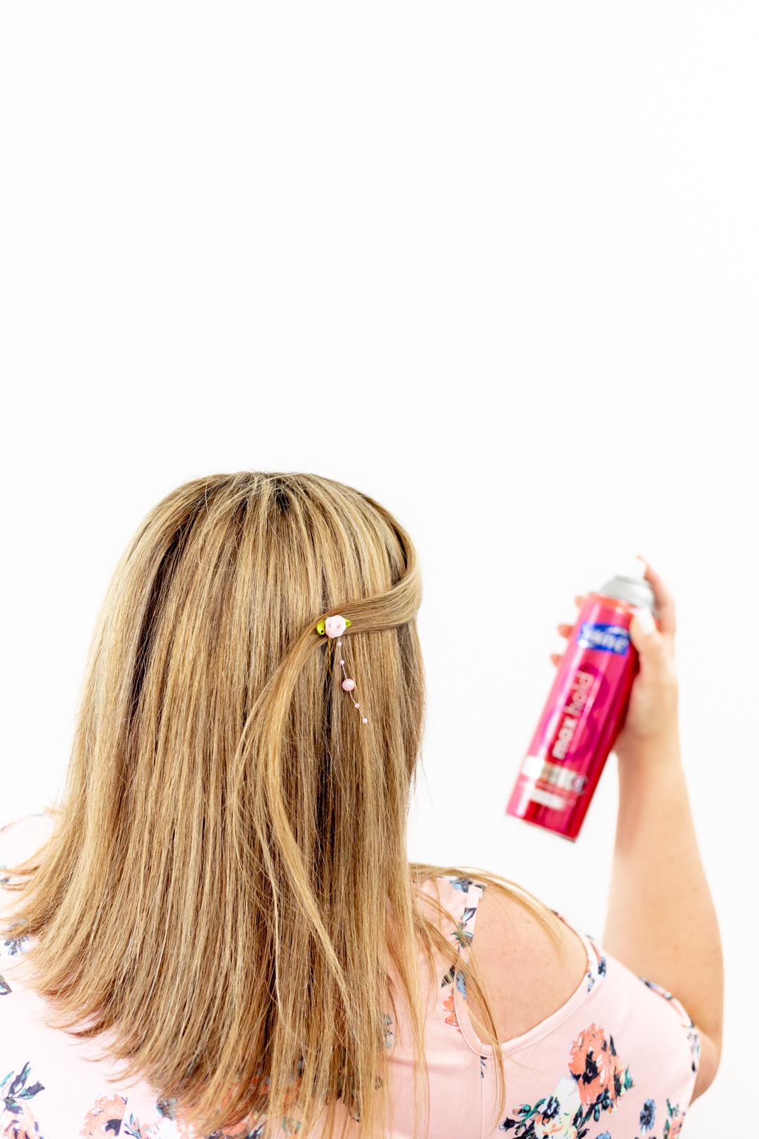 spraying hairspray onto spring hairstyle