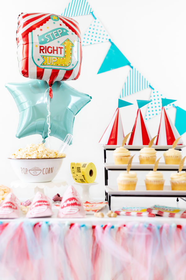 Carnival party table with cupcakes, balloons, popcorn and peanuts