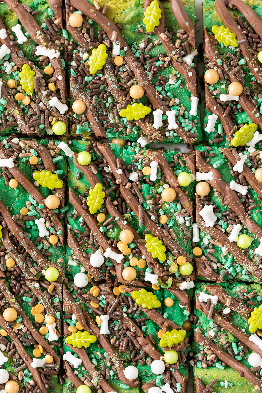 Dinosaur bars with drizzled chocolate frosting and edible dino sprinkles
