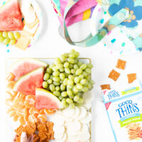fruit and cheese snack board with grapes, watermelon, mandarin oranges and cheese