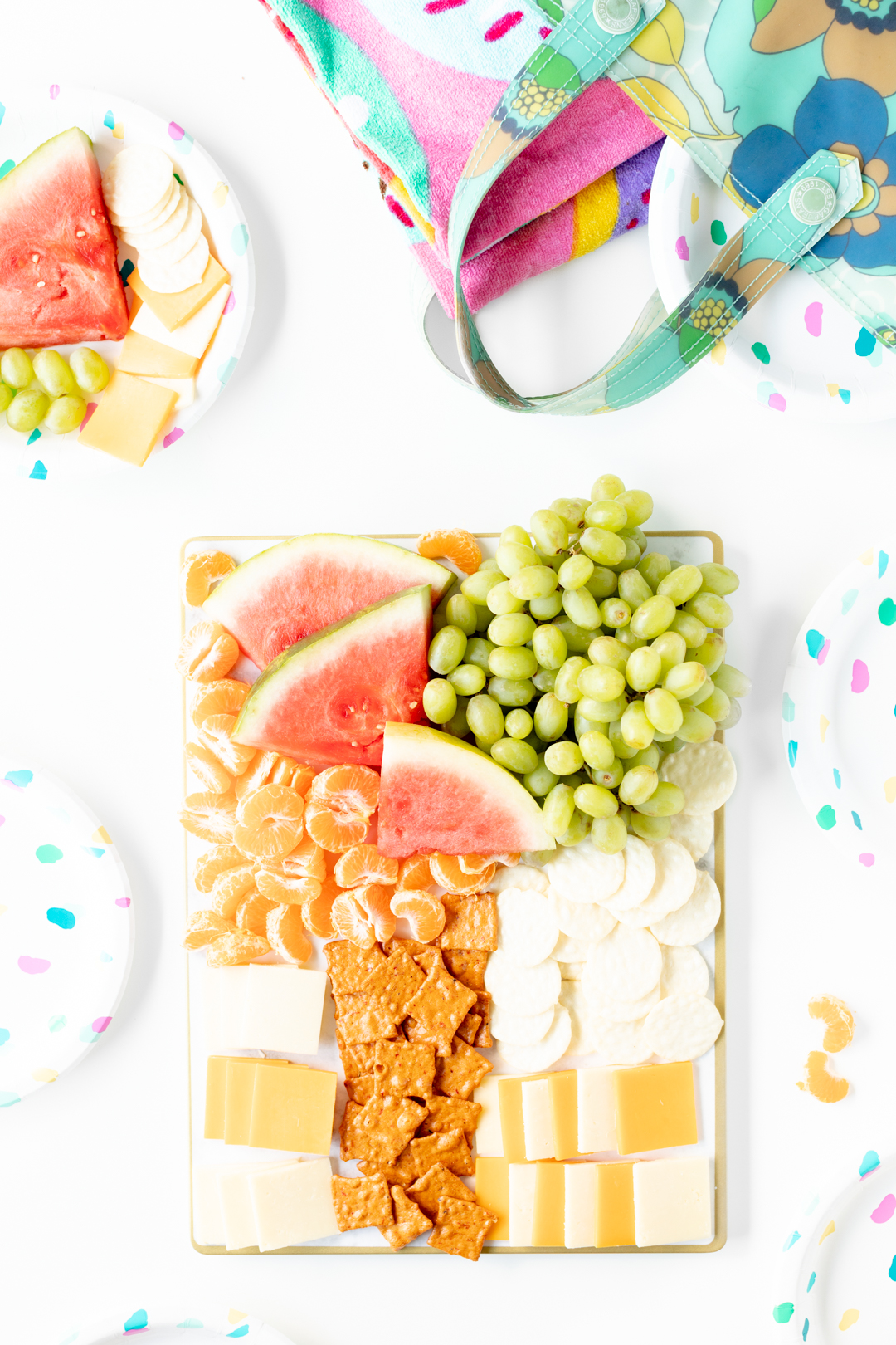 watermelon, grapes, mandarins, cheese and crackers on a tray