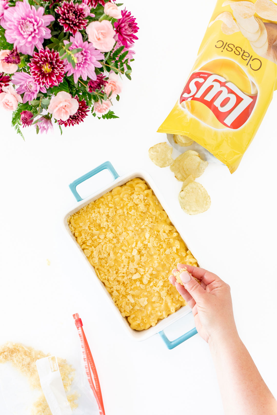 putting crushed potato chips on top of mac and cheese in a casserole dish